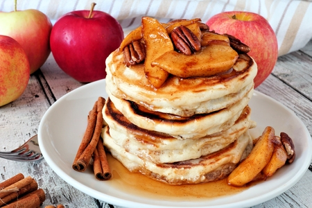 pecan: Autumn pancake stack with baked apples, pecans and cinnamon topped with maple syrup, table scene Stock Photo