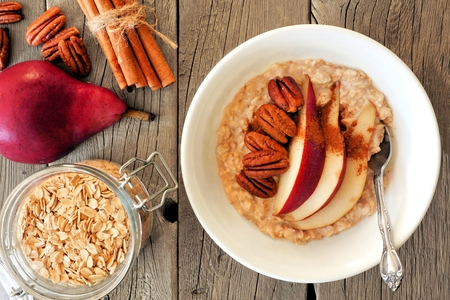 pecans: Autumn breakfast oatmeal with red pear, pecans and cinnamon, overhead scene on rustic wood Stock Photo