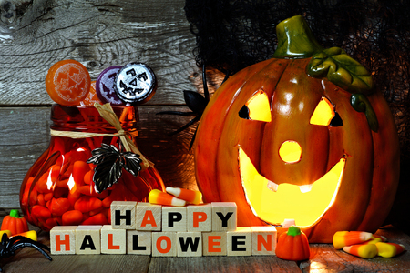 Happy Halloween wooden blocks with jack o lantern and candy, night scene against an old wood background