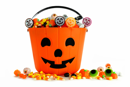 Halloween Jack o Lantern candy collector with scattered candy over a white background