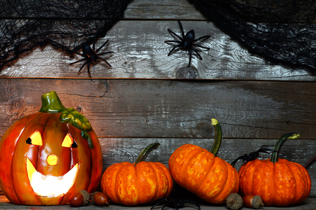 mini jack: Halloween Jack o Lantern lit at night with pumpkin bottom border against a rustic old wood background Stock Photo