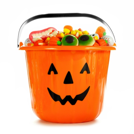 filled: Halloween Jack o Lantern candy collector filled with candy over a white background