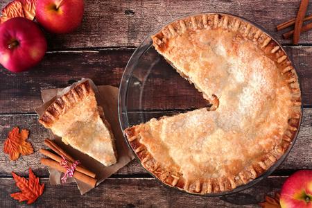 Autumn apple pie, overhead table scene with cut slice on rustic wood