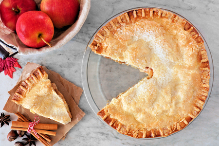 Apple autumn pie, overhead scene with cut slice on marble background Stock Photo