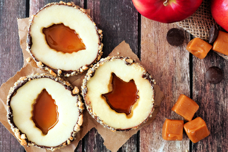 yummy: Autumn apple rounds with caramel filled centers, above view on rustic wood