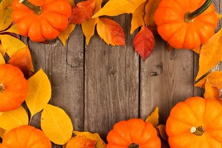 hojas antiguas: Marco del otoño de las calabazas y las hojas contra un fondo rústico de madera vieja