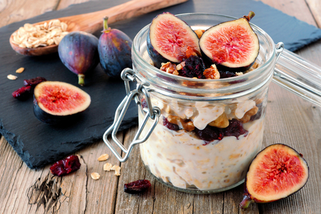 fig fruit: Jar of overnight autumn oats with red figs, cranberries and walnuts against a rustic wood background