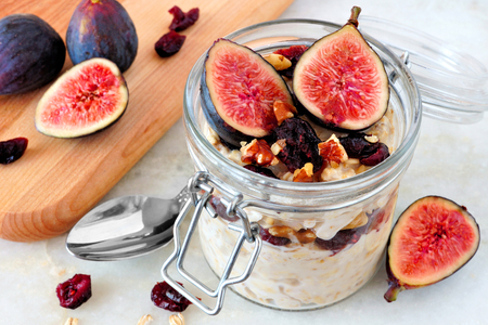 Jar of overnight autumn oats with red figs, cranberries and walnuts against a marble background
