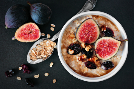 Oatmeal with red figs, cranberries and walnuts in a bowl, above view on dark slate