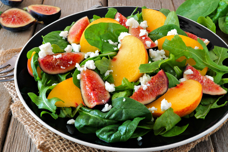 goat peach: Autumn salad of arugula, spinach figs and goat cheese in a black plate on a rustic wooden background