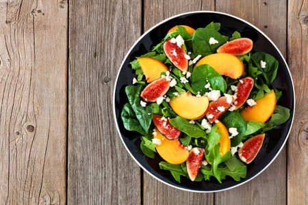 goat peach: Autumn salad of arugula, spinach figs and goat cheese in a black plate, above view on a rustic wooden background Stock Photo