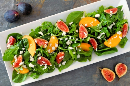 goat peach: Autumn salad of arugula, spinach figs and goat cheese in a white rectangular plate, overhead scene on slate Stock Photo