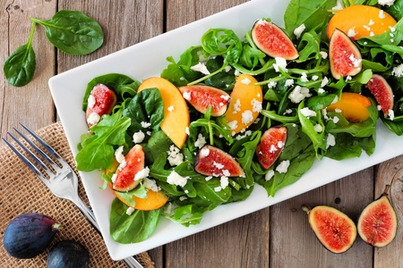 Autumn salad of arugula, spinach figs and goat cheese in a white rectangular plate, overhead scene on rustic wood