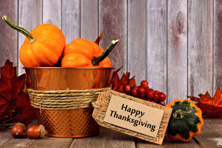 Happy Thanksgiving tag, pumpkins, leaves and autumn home decor with rustic wood background