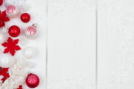 red and white christmas ornament side border with snow frame on a white wood background stock
