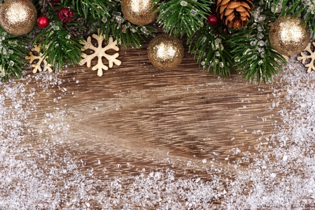 Christmas top border with gold ornaments, branches and snow frame on a rustic wood background