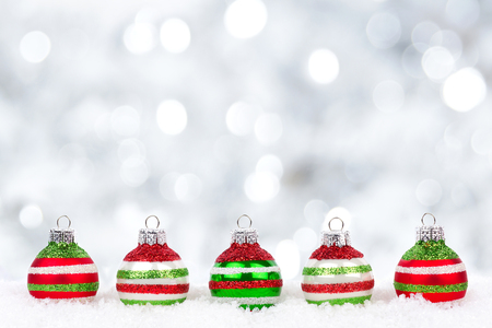 Red, green and white Christmas ornaments in snow with twinkling silver background