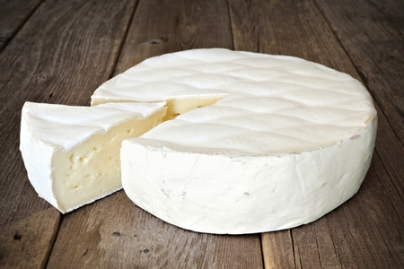 Brie cheese against a rustic wooden background with cut slice