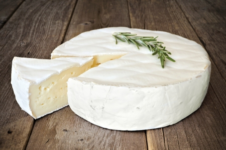 Brie cheese against a rustic wooden background with rosemary and slice cut Imagens