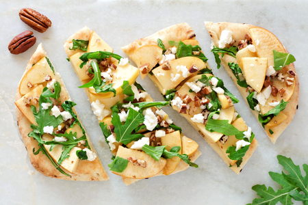 Flat bread with apples, arugula, feta and pecans, above view on white marble