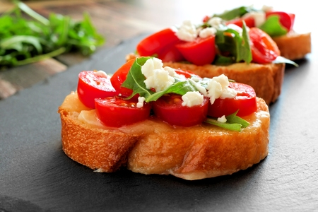 Crostini appetizers with cherry tomatoes, arugula, and cheese, close up on slate server