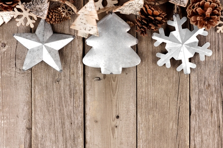 Rustic Christmas top border with metal ornaments on an aged wood background