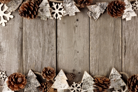 Rustic Christmas double border with wood ornaments and pine cones on an aged wood background Banco de Imagens