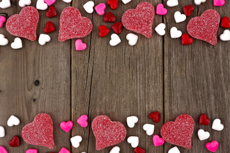 Valentines Day heart shaped candy double border on a rustic wood background