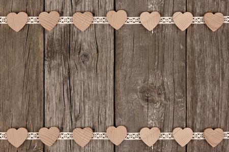 Borde doble de los corazones de madera y cordón de la cinta sobre un fondo de madera rústica Foto de archivo - 69577628