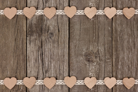 downward: Double border of wooden hearts and ribbon lace over a rustic wooden background
