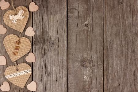 Borde lateral de corazones de arpillera hechos a mano con cinta y botones sobre un fondo de madera rústica