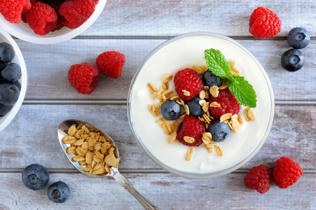 Greek yogurt with sweet berries and granola, overhead scene on rustic wood