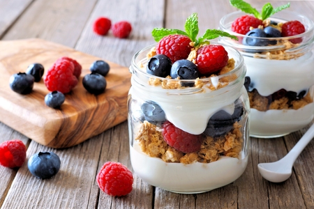 Blueberry and raspberry parfaits in mason jars, scene on a rustic wood background
