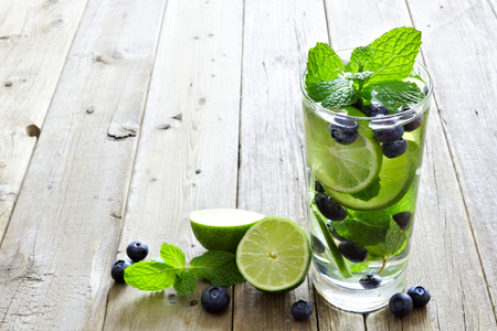 flavoured: Glass of blueberry, lime, mint detox water against a rustic wood background