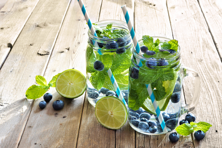 cleanse: Two mason jar glasses of blueberry, lime, mint detox water with straws against a rustic wood background Stock Photo