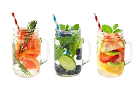 flavoured: Three types of fruit detox water in mason jar glasses with straws isolated on a white background