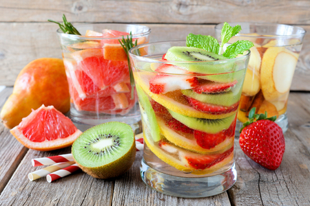 flavoured: Assortment of fruit infused water in glasses against a rustic wood background