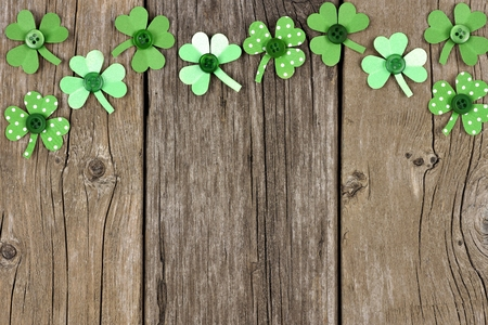 paddys: St Patricks Day top border of handmade paper shamrocks over a rustic wood background Stock Photo