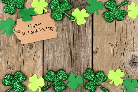 saint paddy's: Happy St Patricks Day tag with double border of shiny shamrocks over a rustic wood background Stock Photo