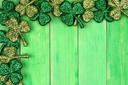 St Patricks Day corner border of shiny glitter shamrocks over a green wood background