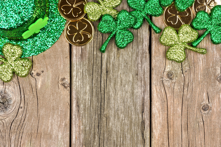 St Patricks Day top border of shamrocks, gold coins and leprechaun hat over rustic wood