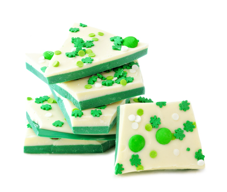 bark background: St Patricks Day chocolate candy bark with shamrock sprinkles, stacked over a white background