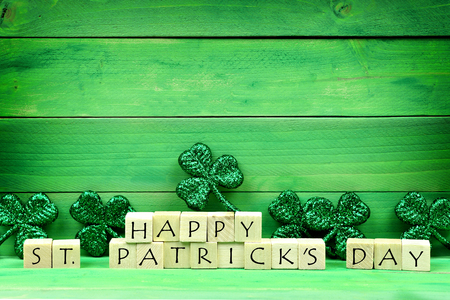 paddys: Happy St Patricks Day wooden blocks with shiny shamrocks over a green wooden background
