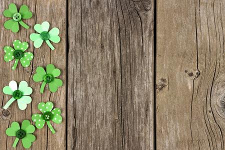 cloverleaf: St Patricks Day side border of handmade paper shamrocks over a rustic wood background
