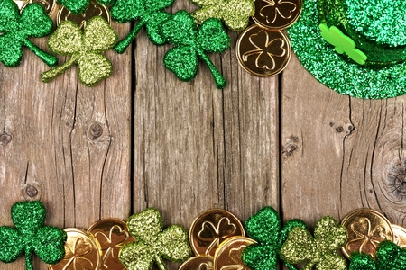 St Patricks Day double border of shamrocks, gold coins and leprechaun hat over rustic wood