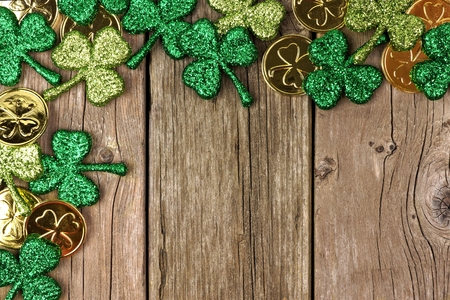 St Patricks Day corner border of shamrocks and gold coins over a rustic wood background Archivio Fotografico