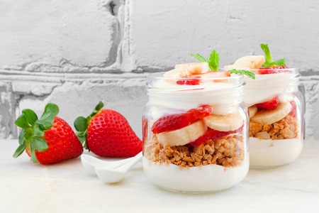 Strawberry and banana parfaits in mason jars, still life against a white brick background
