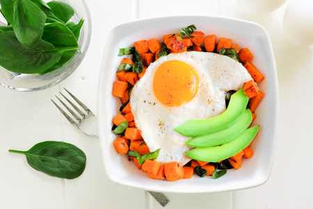 Breakfast nutrient bowl with sweet potato, egg, avocado and spinach overhead scene on white wood