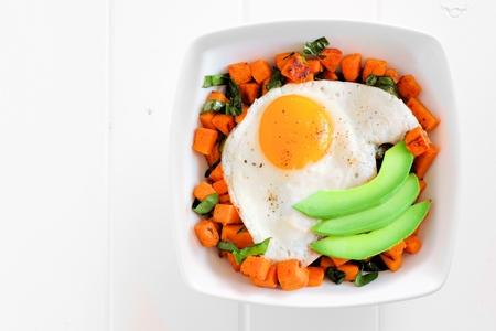 nutrients: Breakfast nutrient bowl with sweet potato, egg, avocado and spinach above view on white wood Stock Photo