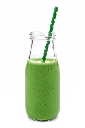 白い背景に分離した牛乳瓶で緑のスムージー